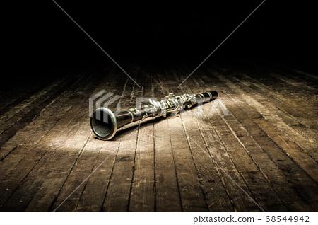 a black woodwind clarinet lies on a dark brown 68544942