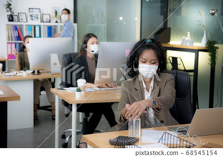 Asian woman office worker wearing face mask working in new normal office and doing social distancing 68545154