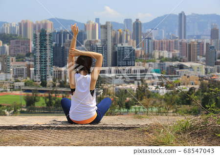 sporty woman take exercise in front of the skyline of city 68547043
