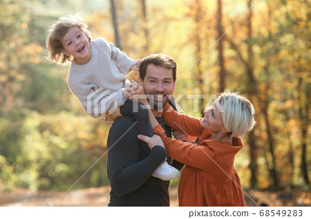 Beautiful young family with small daughter on a walk in autumn forest. 68549283