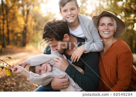 Beautiful young family with small children on a walk in autumn forest. 68549284