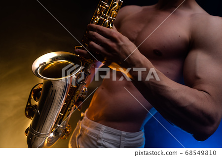 Muscular man naked torso playing on saxophone with smoked colorful background  68549810
