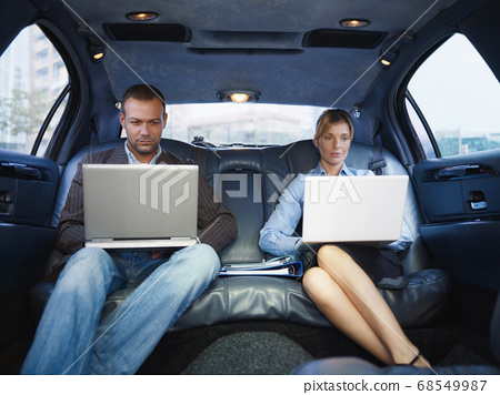 Business Man And Woman Working With Laptop In Limousine 68549987