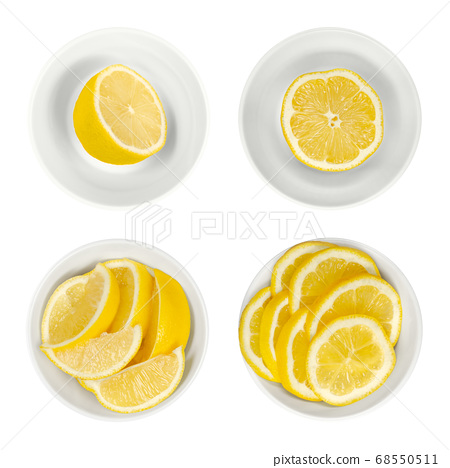 Lemons in white glass bowls. Freshly cut lemon halves, wedges and slices. Ripe and yellow citrus fruits, used for culinary purposes. Citrus limon. Close up from above, isolated over white, food photo. 68550511