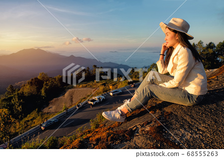 Happy woman siting on green grass meadow on top of 68555263