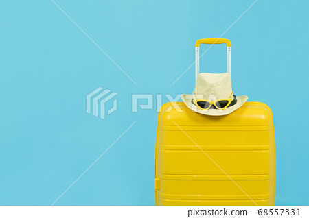 Summer holidays, vacation and travel concept.Yellow Suitcase or luggage bag and the fashion sunglasses on hat isolated on blue background with copy space 68557331
