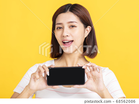 happy young woman showing blank screen mobile 68562086