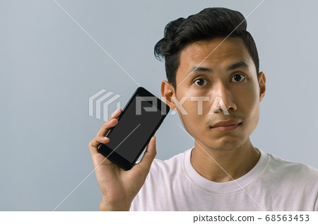 Asian Man is Hesitated to Using the Mobile Phone. 68563453