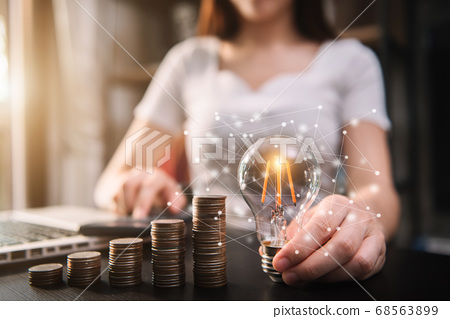 Business woman hand holding lightbulb with coins stack on desk. concept saving energy and money at office. 68563899