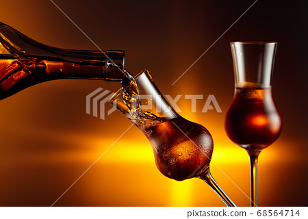 Pouring an alcoholic beverage into a steamed glass 68564714