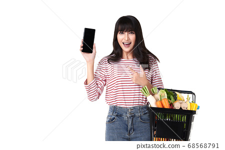 Happy Asian woman with smartphone holding basket 68568791