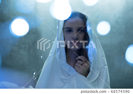 Mad woman in garlands sitting in bed, insomnia 68574390