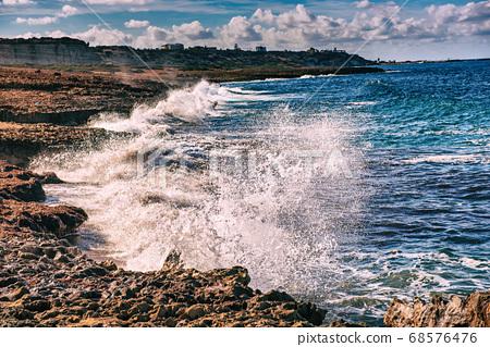Sea splashing on rocks 68576476