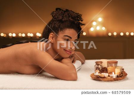Black woman enjoying hot stone spa treatment 68579509