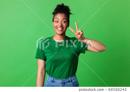 Excited afro girl showing v sign looking at camera 68580243