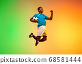 Male soccer, football player training in action isolated on gradient studio background in neon light 68581444