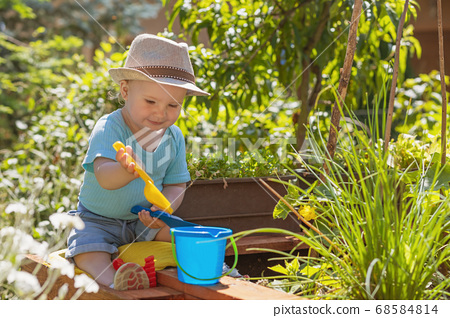 Baby boy is playing with kids garden tools 68584814