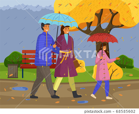 Family walking in the rain with umbrella and wearing raincoats in the city park in autumn season 68585602