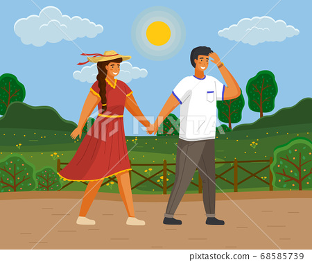 Couple walking in a park. Young guy and girl wearing a light dress and a straw hat holding hands 68585739