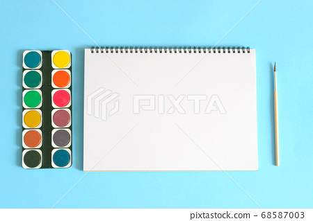 Art concept. Back to school. Watercolors with white notebook and brush on blue background.  68587003