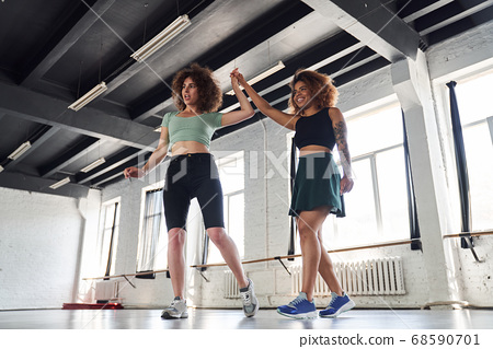 Smiling young ladies practicing modern dances in sport class 68590701