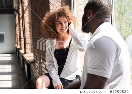 Cheerful beautiful woman talking with man indoors 68590886