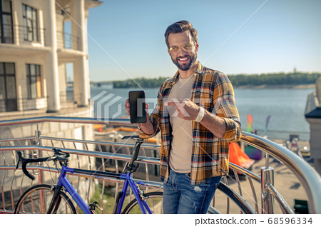 Man with smartphone pointing finger at him 68596334