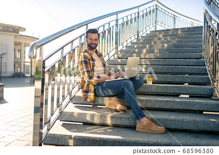 Attractive man sitting with laptop on stairs 68596380
