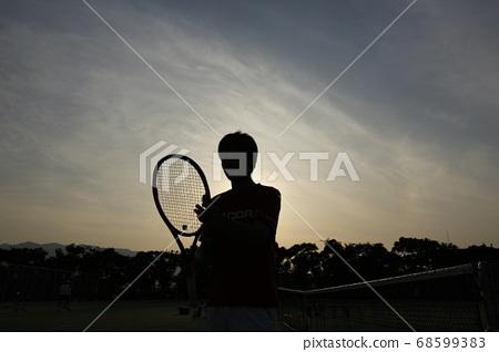 晚上有网球拍的球员 68599383