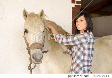 Beautiful young girl and white horse 68605933