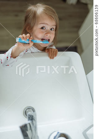 Baby girl in bright bathroom brushing her teeth above the sink. 68606139