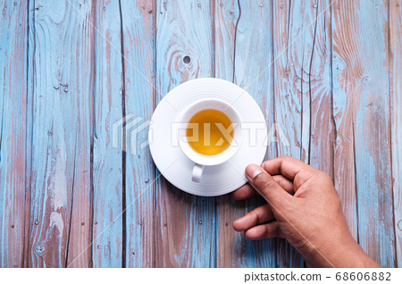 man holding hot cup of tea on table . 68606882