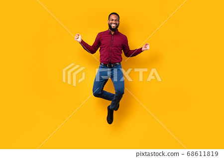 Happy black guy jumping and looking at camera 68611819