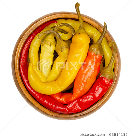 Peperoni pickles in a wooden bowl. Pickled whole chili peppers of different bright colors. Vegetable, preserved in brine. Capsicum. Close-up from above, on white background, isolated macro food photo. 68614152
