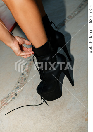 A striptease dancer is tying the laces on classic black pole dancing shoes high heels 68615816
