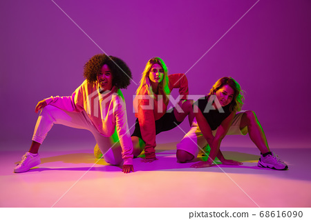 Sportive girls dancing hip-hop in stylish clothes on gradient background at dance hall in neon light 68616090