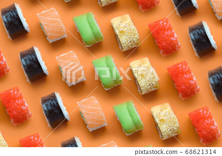 Different types of asian sushi rolls on orange 68621314