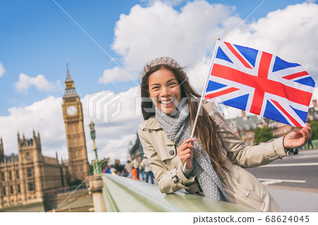 London travel tourist woman showing Union flag Great Britain british UK flag. Asian girl at Big Ben on Westminster bridge on Europe holidays holding icon at iconic landmark 68624045