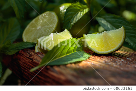 Lime slices and mint leaves on an old wooden 68633163