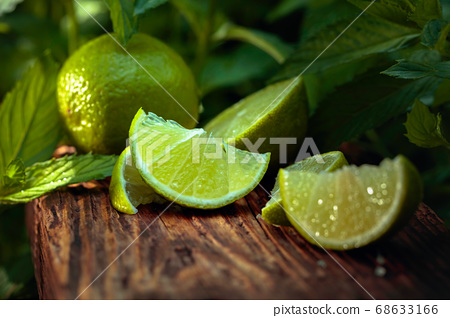 Lime slices and mint leaves on an old wooden 68633166