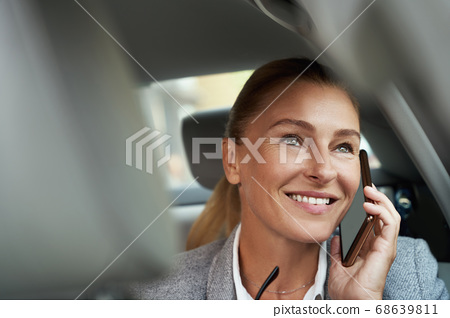 Good talk. Portrait of successful attractive business woman talking by mobile phone and smiling while sitting on back seat in the car 68639811