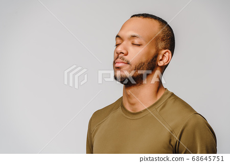 african-american young man in green t-shirt over light grey background with eyes closed with copy space 68645751