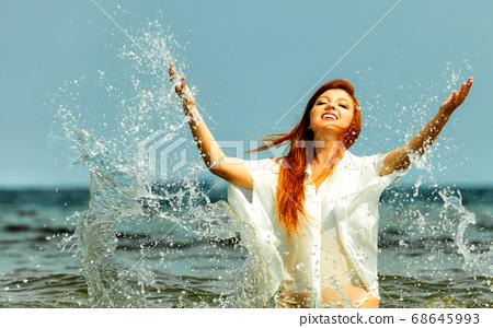 Vacation. Girl splashing water having fun on the 68645993