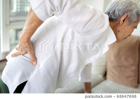 Sad asian senior woman with back and hip joint painful while standing up,female patient having backache,lumbago pain,hand touch on the hip,elderly suffer from ribs hurt or waist pain,health problems 68647698
