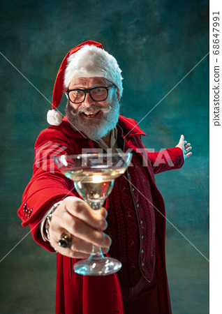 Modern stylish Santa Claus in red fashionable suit and cowboy's hat on dark background 68647991