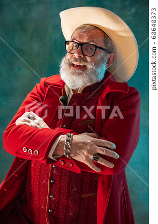 Modern stylish Santa Claus in red fashionable suit and cowboy's hat on dark background 68648373