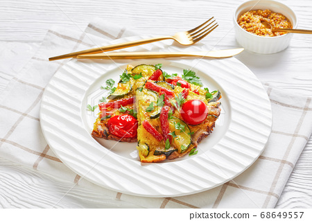 omelet with zucchini, smoked sausages and tomatoes 68649557