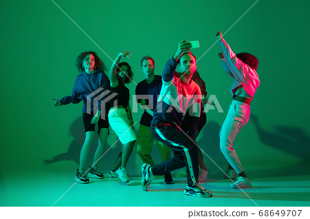 Stylish men and woman dancing hip-hop in bright clothes on gradient background at dance hall in neon light 68649707