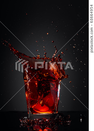 Cola glass with lemon and falling ice cubes. 68664954