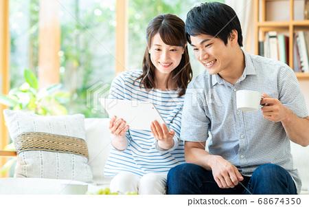 在客廳裡使用平板電腦的年輕夫婦 68674350